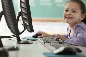 Hispanic girl using computer in classroom