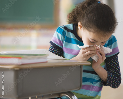 Hispanic girl blowing nose in classroom