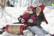Hispanic girls sledding down snow covered hill