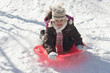 Hispanic girl sledding on snow covered hill