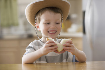 Caucasian boy in cowboy hat eating sandwich