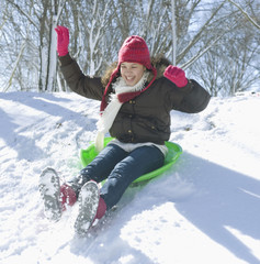 Hispanic girl sledding down snow covered hill