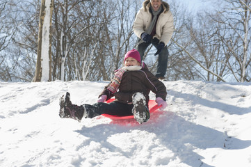 Father watching daughter sledding down snow covered hill