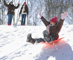 Hispanic girl sledding down snow covered hill