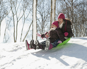 Hispanic girls sledding down snow covered hill
