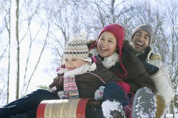Father and daughters sledding down snow covered hill