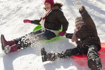 Hispanic girls sledding on snow covered hill