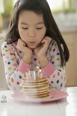 Mixed race girl blowing out candles on pancakes