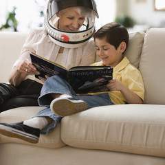 Caucasian grandmother reading space book to grandson