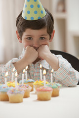 Caucasian boy sitting with birthday cupcakes