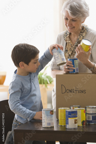 Caucasian grandmother and grandson filling box with canned goods for charity