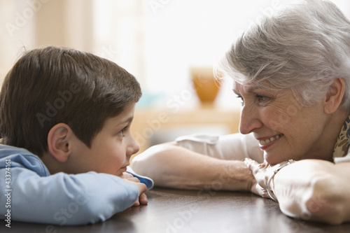 Caucasian grandmother and grandson smiling at each other