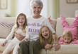 Caucasian grandmother and granddaughters sitting on sofa together