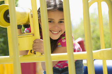 Hispanic girl playing on playground structure
