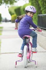 Hispanic girl riding bicycle with training wheels