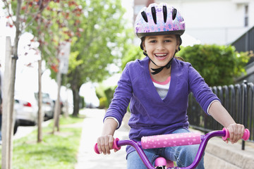 Hispanic girl riding bicycle on sidewalk