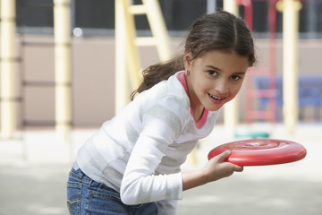 Hispanic girl throwing plastic disc on playground