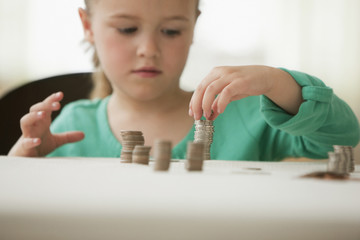 Caucasian girl stacking coins