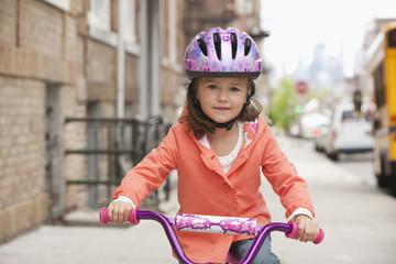 Caucasian girl riding bicycle on urban sidewalk