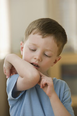 Caucasian boy looking at wound on elbow