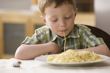 Caucasian boy eating pasta noodle