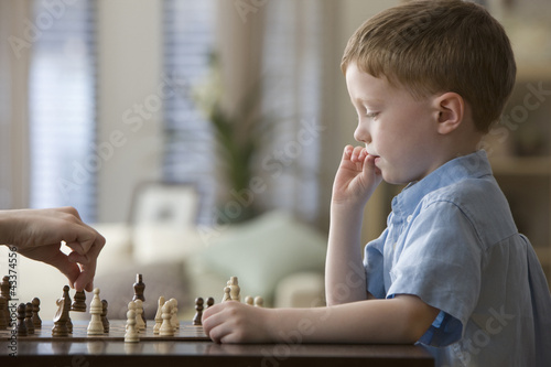 Caucasian boy playing chess