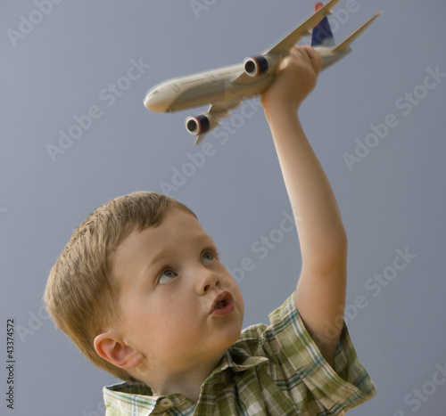 Caucasian boy playing with model airplane