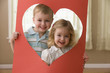 Caucasian brother and sister looking through heart-shape cut-out