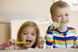 Caucasian brother and sister brushing teeth