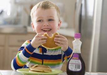 Caucasian boy eating pancakes