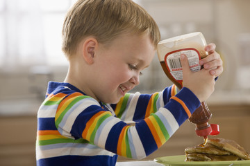 Caucasian boy pouring syrup on pancakes