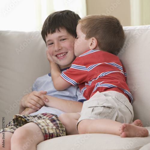Boy kissing brother on sofa