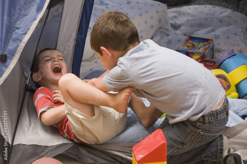 Caucasian boys playing in tent