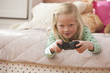 Caucasian girl laying on bed playing video game