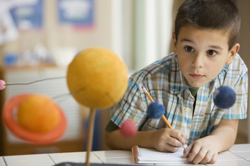 Mixed race boy studying the planet model in classroom