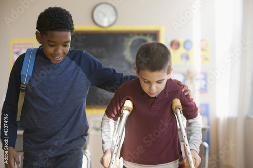 Boy walking with friend on crutches
