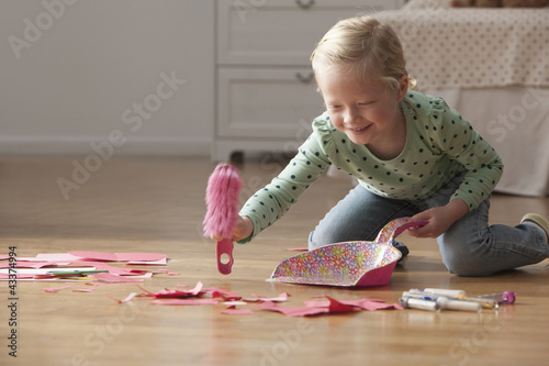 Caucasian girl cleaning up mess from floor