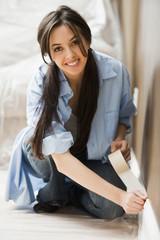 Caucasian woman taping wall