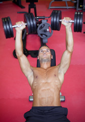 Handsome fit man doing a chest exercise at the gym
