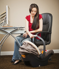 Caucasian woman sitting at home office looking at baby
