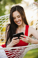 Caucasian woman in hammock text messaging on cell phone