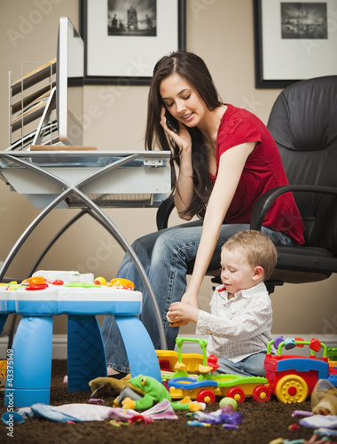 Caucasian woman tending child and working in home office