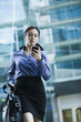 Caucasian businesswoman looking at cell phone outdoors