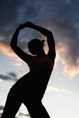 Caucasian woman stretching before exercise at sunset