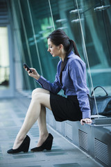 Caucasian businesswoman sitting outdoors using cell phone