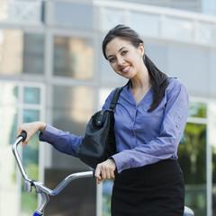 Caucasian businesswoman riding bicycle
