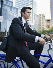Caucasian businessman riding bicycle