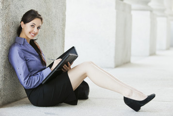Caucasian businesswoman writing in notebook outdoors