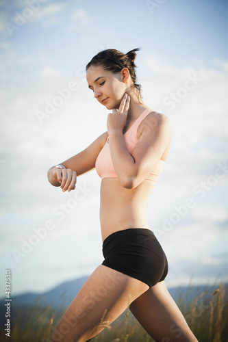 Caucasian woman checking her pulse after exercise
