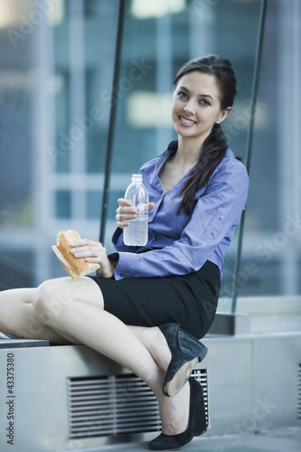 Caucasian businesswoman eating lunch